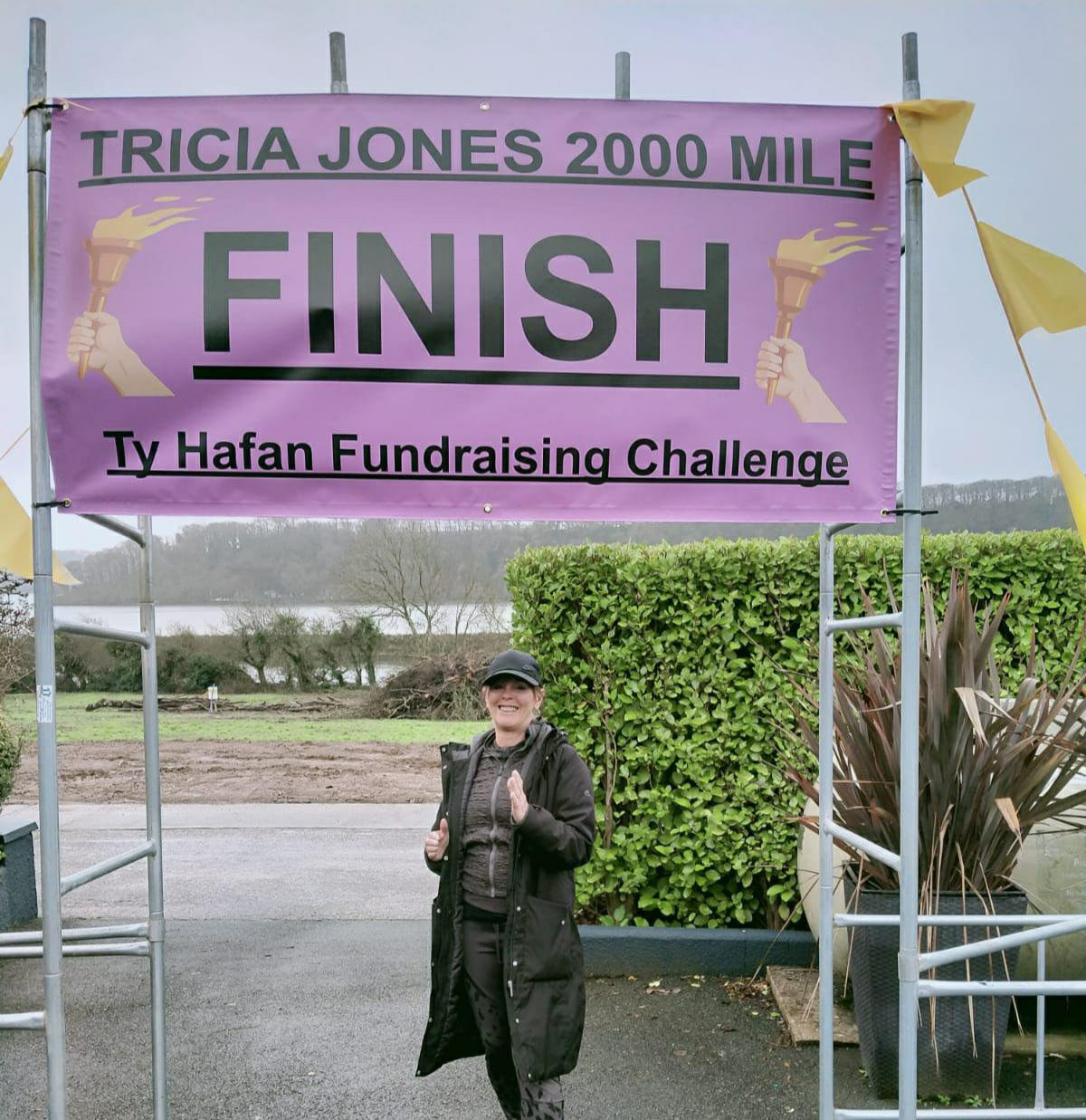 Tricia Jones underneath the finish line banner her husband, Ian, made to celebrate her efforts